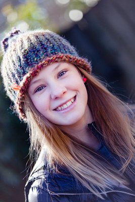 Headshot of 12 year old girl with face filling the frame.  Outdoor photo in the winter with a hat on.