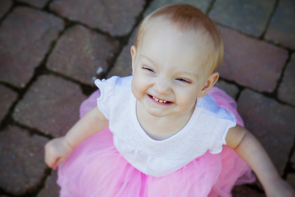 Big grins from a one year old little girl wearing a pink tutu and loving life.