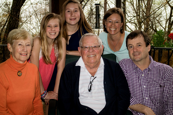 Grandma and grandpa in an outdoor photograph with their daughter, son in law and two teenage grandaughters