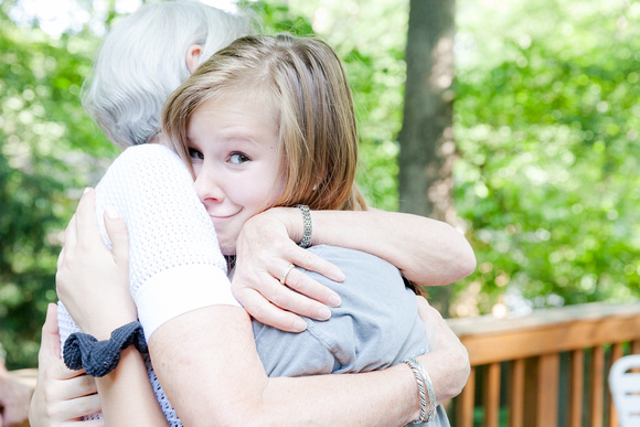 grandmother and granddaughter hugging outside on the porch