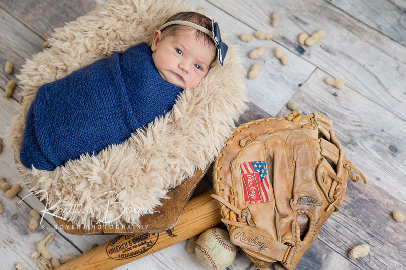 Newborn Baby Girl Portraits with infant wrapped in a blue wrap and surrounded by softball glove, bat, on a wood floor and covered in peanuts.
