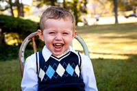 toddler boy wearing argyle and laughing during school photos outside