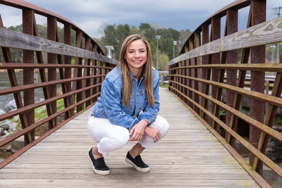 Senior Portrait Photograph of High School Senior on a metal bridge on a stormy day