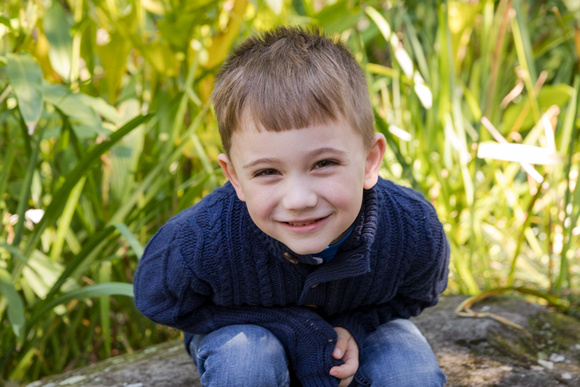 Young boy grinning a huge grin at the camera during his fall family photos with the sun streaming through the plants behind him.