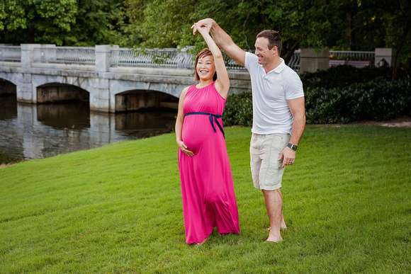 Maternity photos in Midtown Atlanta with husband and wife dancing by the lake