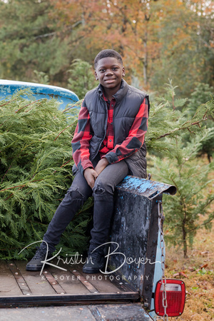 A beautiful family with two teenage boys at a Christmas Tree Farm photo shoot wearing red and black and posing on a old blue vintage Ford Pickup truck.