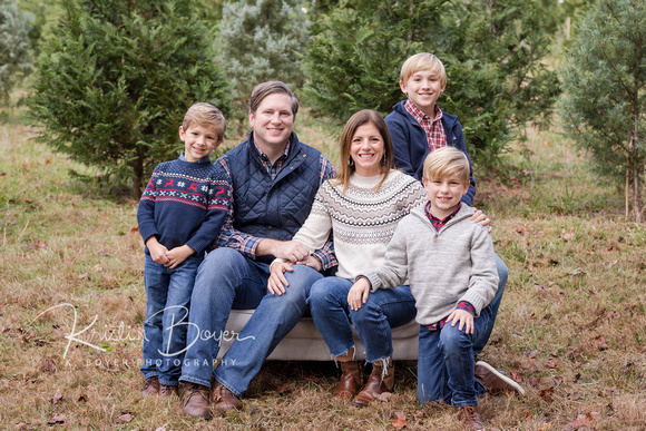 young family at a christmas tree farm in atlanta ga in November sitting on a small white couch outside and wearing navy, red and cream sweaters and blue jeans.