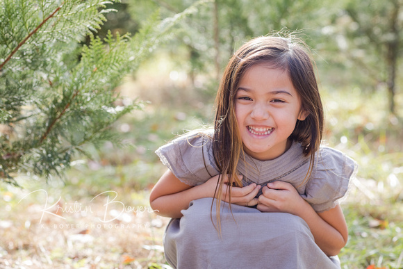 Smiles of joy from a little girl running around a Christmas tree farm in November