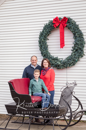 Family in an old antique sleigh with a giant Christmas wreath behind them .