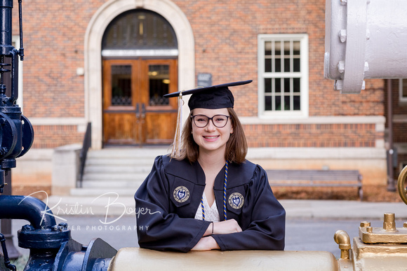 Gorgeous Young lady in a Cap and Gown for Senior Portrait photos in Front of the Steam Engine at Georgia Tech