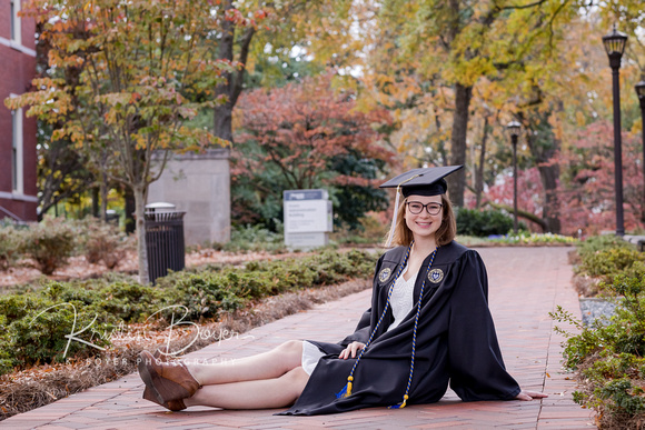 Gorgeous Young lady in a Cap and Gown for Senior Portrait photos in Front of Tech Tower at Georgia Tech, Sitting down on a red brick pathway with fall trees, tall black street lights and a cap and gown for graduation photos at Georgia Institute of Technology.