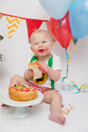 First Birthday Cake Smash photos with a one year old little boy and a pizza theme.  Darling balloons, pizza boxes and primary color decorations on a white background.  Great birthday party theme for a boy