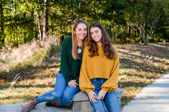 2 beautiful sisters posing for mini session family photos together on a beautiful fall day.