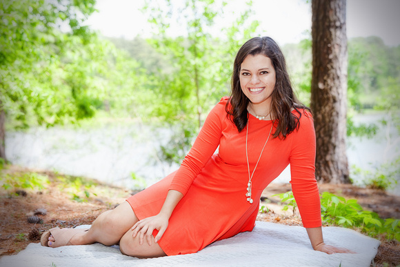 Graduating Senior Portrait sitting outside on a blanket in an orange dress in front of a lake in North Atlanta's Murphey Candler park