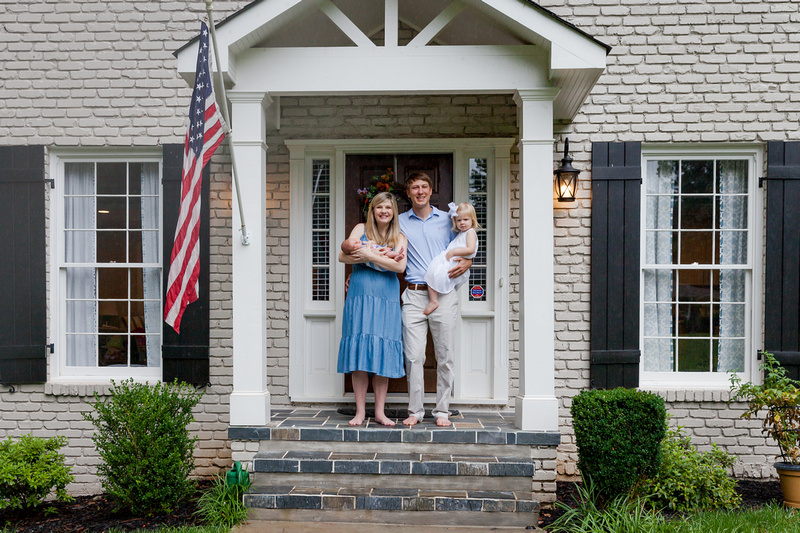 Brand new family of four with a newborn baby standing on the front door of their porch