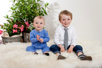 Studio preschool portraits with cream backdrop, spring flowers, soft fluffy cream rug and darling toddlers and infant children